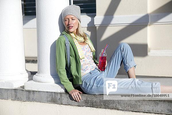 Junge Frau lehnt sich an die Säule und hält Erfrischungsgetränk.