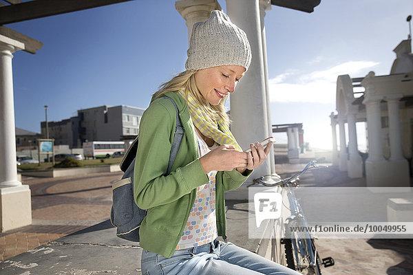 Junge Frau sitzt draußen und schaut auf das Handy