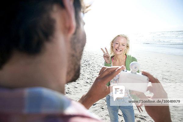 Mann fotografiert glückliche Frau am Strand
