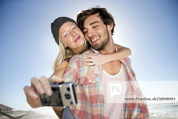 Junge Frau auf dem Rücken ihres Freundes am Strand  die einen Selfie nimmt.