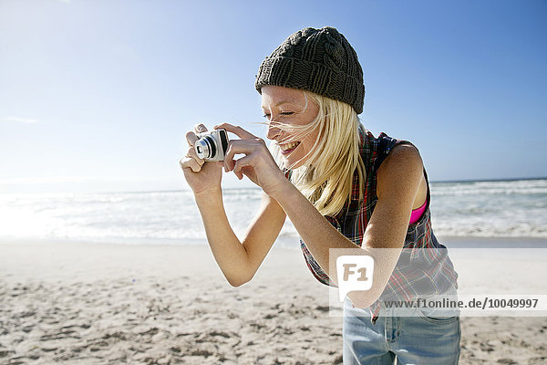 Young woman taking picture on the beach