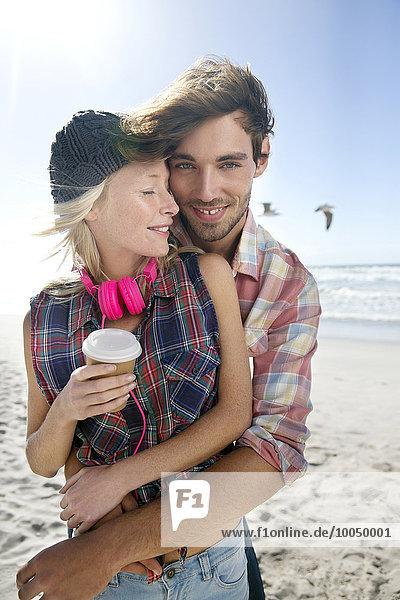 Glückliches junges Paar  das sich am Strand umarmt.