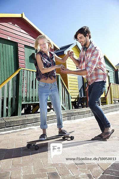 Junger Mann hilft Freundin auf Skateboard in bunten Strandhütten