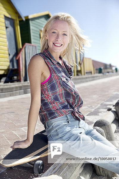 Fröhliche junge Frau mit Skateboard an der Strandpromenade