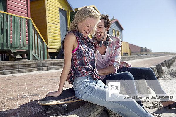 Glückliches junges Paar mit Skateboard an der Strandpromenade