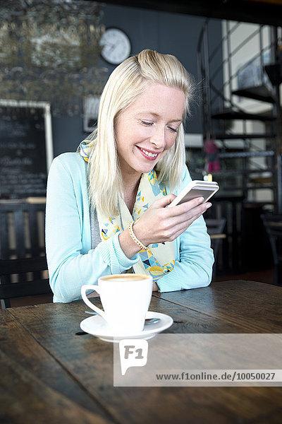 Junge Frau in einem Café  die auf ihr Handy schaut