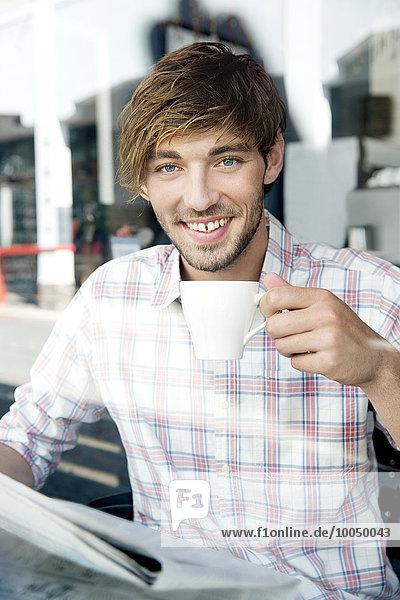 Porträt eines lächelnden jungen Mannes in einem Café