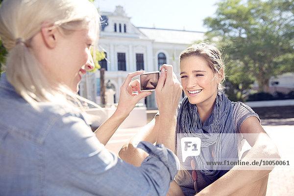 Junge Frau beim Fotografieren eines Freundes im Freien