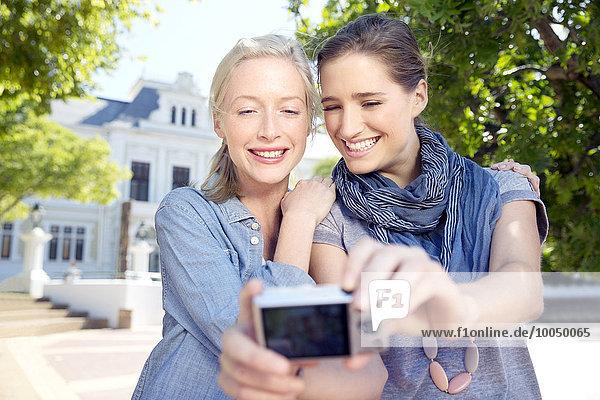 Zwei junge Frauen im Freien mit einem Selfie.