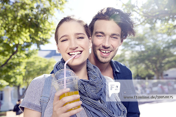 Smiling young couple outdoors with soft drink
