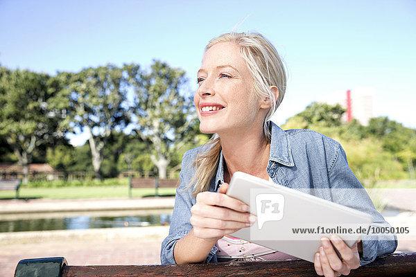 Junge Frau mit digitalem Tablett auf Parkbank