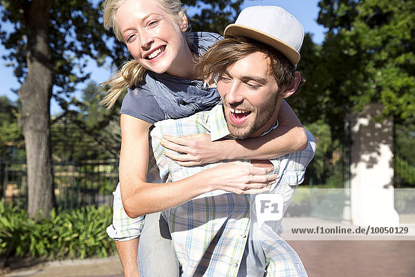 Happy young man carrying girlfriend piggyback