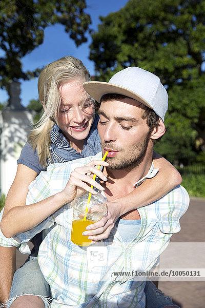 Junger Mann trinkt Erfrischungsgetränk mit Freundin Huckepack