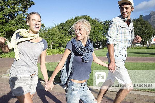 Enthusiastische Freunde laufen Hand in Hand