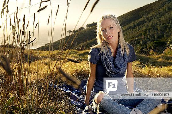 Junge Frau entspannt sich auf einer Decke auf der Wiese