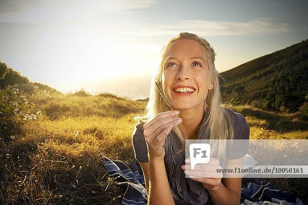 Lächelnde junge Frau in abgelegener Landschaft schaut nach oben