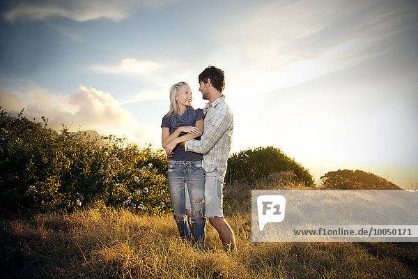 Junges Paar umarmt sich in abgelegener Landschaft