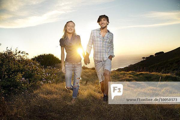 Junges Paar geht Hand in Hand an die Küste