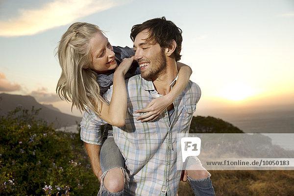 Junger Mann mit Freundin Huckepack an der Küste