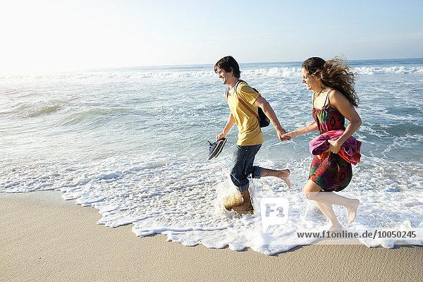 Südafrika  glückliches Paar  das im Ozean läuft