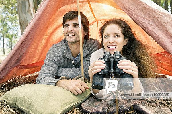 Südafrika  glückliches Paar mit Fernglas im Zelt
