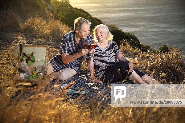 Südafrika  glückliches Seniorenpaar mit Gläsern Rotwein beim Picknick