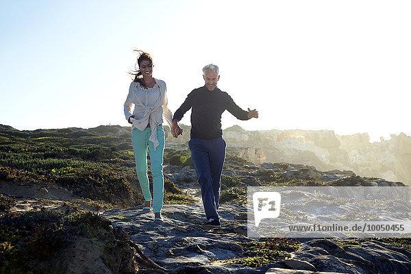 Südafrika  Paar  das Hand in Hand an der Küste entlang läuft