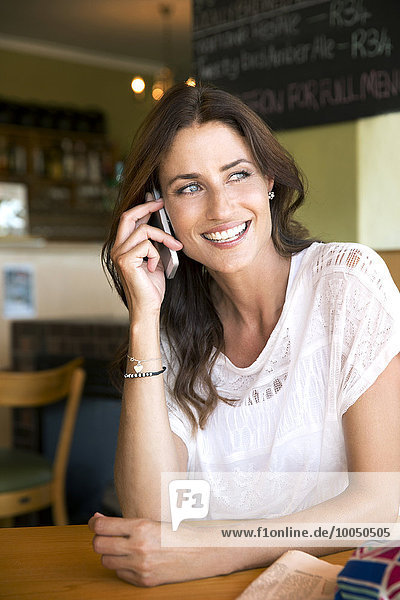 Porträt einer lächelnden Frau beim Telefonieren mit dem Smartphone im Cafe