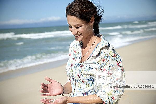 Südafrika  Porträt einer lächelnden Frau mit Muscheln in der Hand