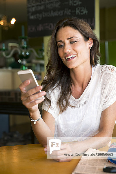 Portrait of smiling woman looking at her smartphone in a cafe