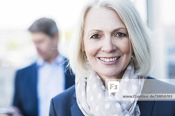 Portrait einer reifen Geschäftsfrau mit Mann im Hintergrund