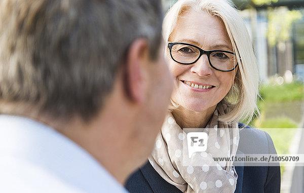 Geschäftsfrau hört dem Geschäftsmann zu