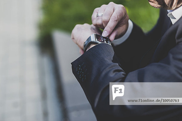 Businessman checking smart watch