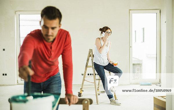 Junge Frau am Telefon mit Mann beim Malen von Holzbrettern im Vordergrund