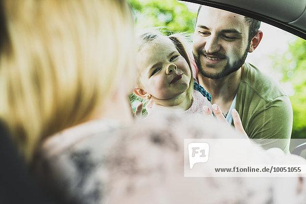 Mädchen mit Vater schaut Mutter im Auto an