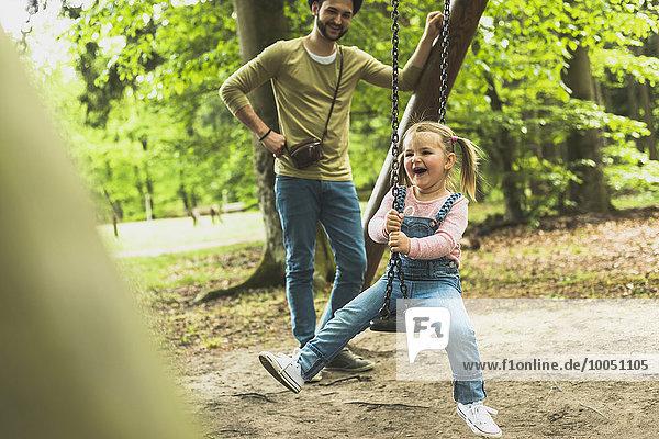 Glückliches Mädchen mit Vater auf dem Spielplatz