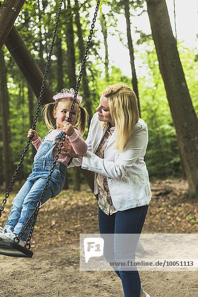 Mutter hält Tochter auf Schaukel