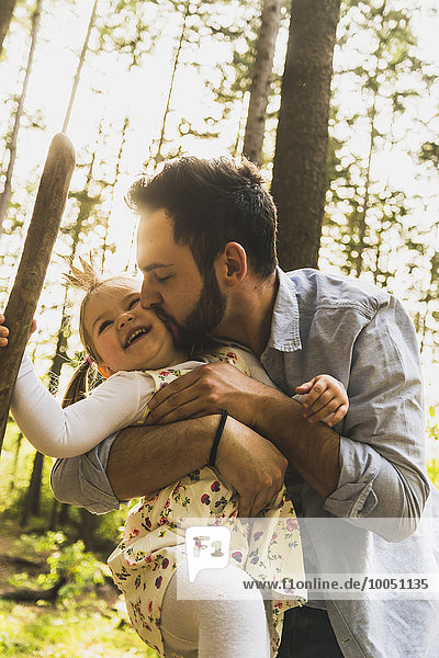 Happy girl with father in forest