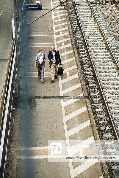 Geschäftsmann und Geschäftsfrau  die auf dem Bahnsteig laufen