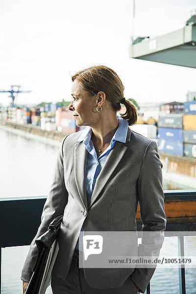 Geschäftsfrau im Containerhafen schaut zur Seite