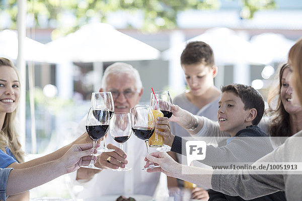 Großfamilie trinkt Rotwein im Restaurant