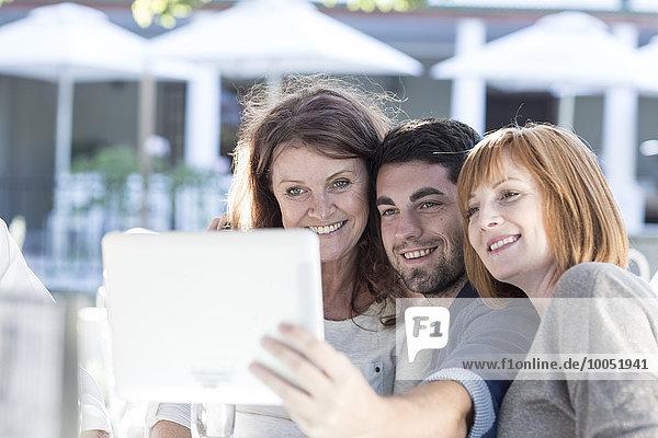 Drei Personen in einem Restaurant fotografieren mit digitalem Tablett