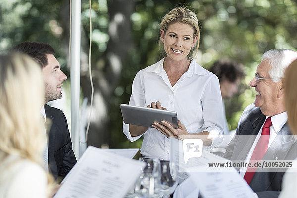 Kellnerin  die ihre Kunden am Tisch mit einem digitalen Tablett zum Mittagessen einlädt.