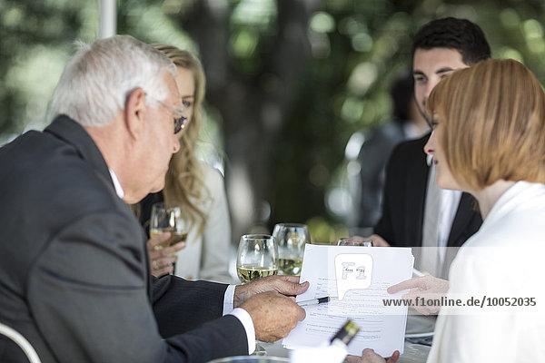 Elegante Leute im Außenrestaurant diskutieren über einen Vertrag