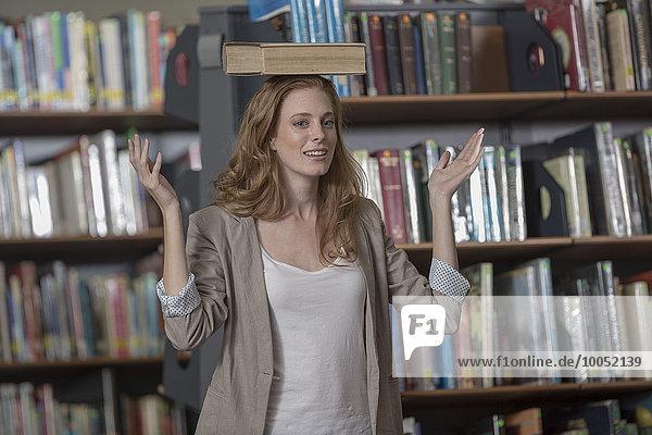 Porträt einer Studentin  die in einer Bibliothek ein Buch auf dem Kopf balanciert.