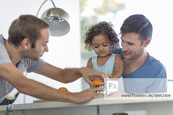 Schwules Paar mit Tochter macht Orangensaft