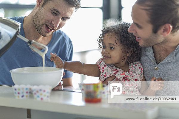 Schwules Paar mit Tochter beim Kuchenbacken