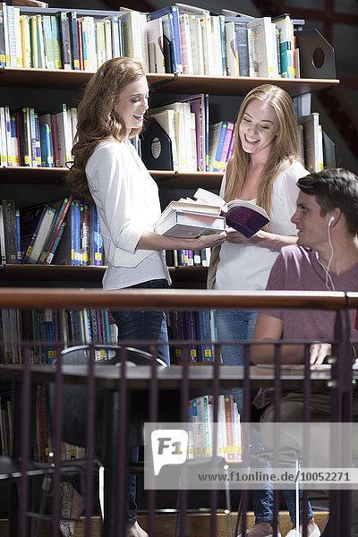 Zwei Studentinnen beim Betrachten von Büchern in einer Bibliothek