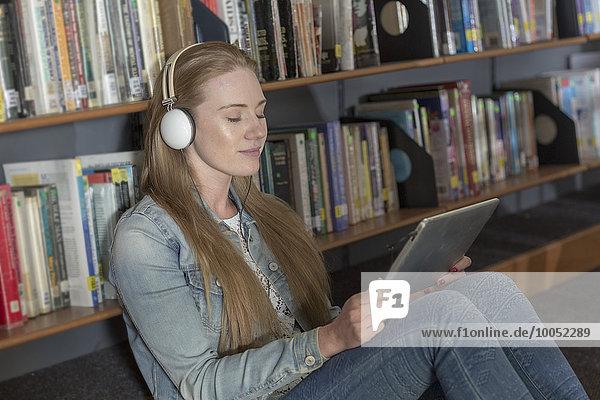 Studentin mit Kopfhörer und digitalem Tablett in der Bibliothek
