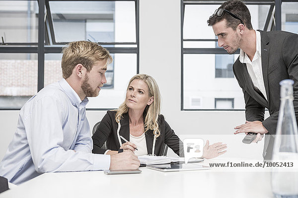 Drei Geschäftsleute bei einem Bürotreffen